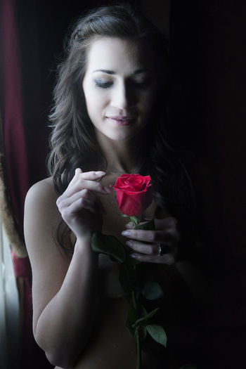 Close-up of woman holding rose at home