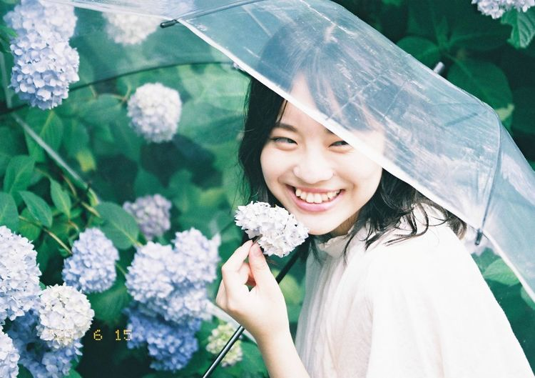 Portrait of a smiling beautiful young woman in rain