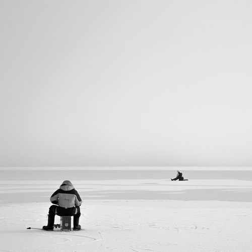 Rear view of man ice fishing on frozen lake