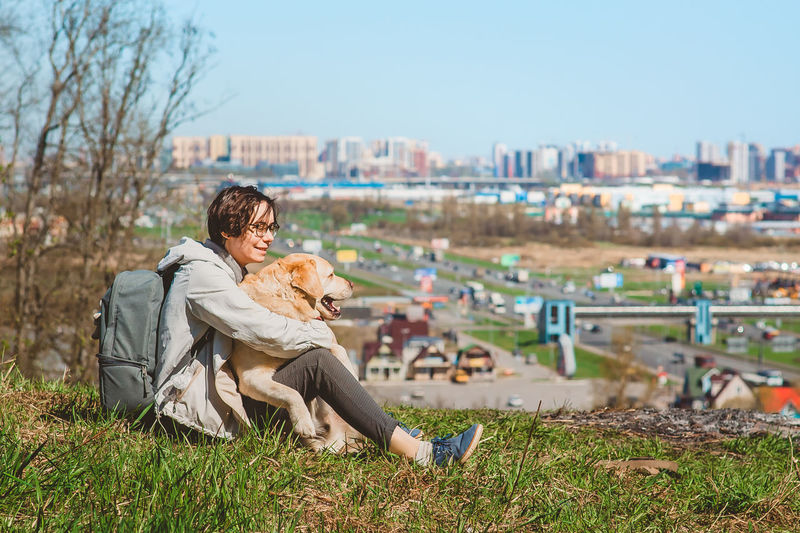 Woman with dog sitting on land