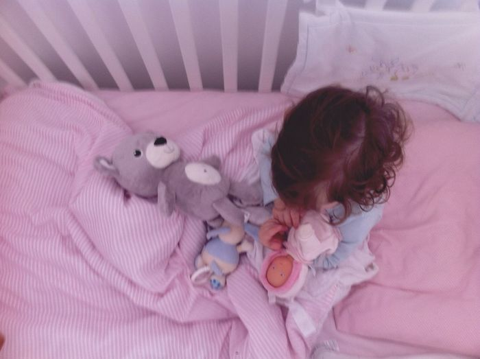 High Angle View Of Girl With Toys In Crib