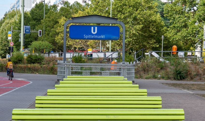 Bench U-Bahnhof Benches Benches In A Row City Communication Day Direction Green Benches Green Color Growth Nature No People Outdoors Plant Road Road Sign Sign Street Symbol Tree