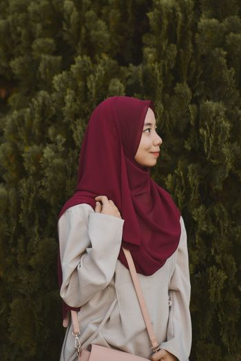 Woman in hijab standing against trees at park