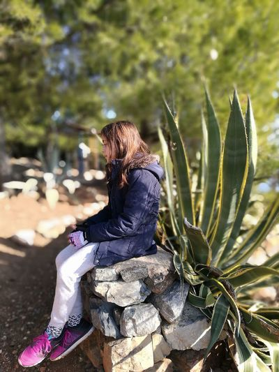 Side view of girl sitting on rocks at field
