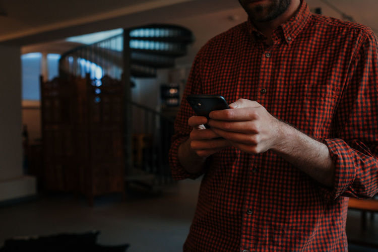 Midsection of man using mobile phone while standing at home