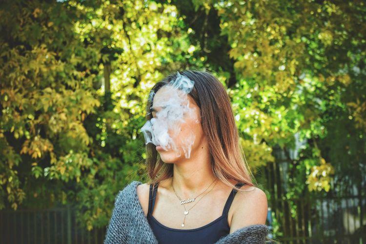 Teenage Girl Smoking Cigarette Against Trees