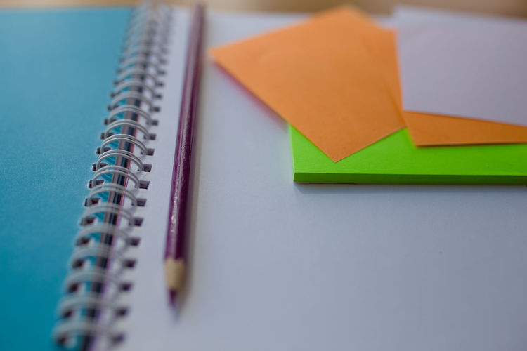 Close-up of adhesive notes and pencil on spiral notebook