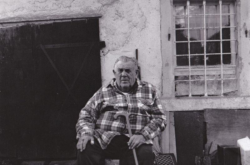Portrait Of Senior Man Sitting Against Old Building