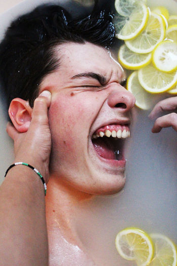 Directly above portrait of man with lemon slices in bathtub
