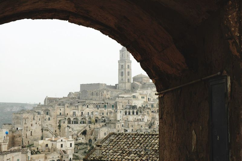 View through archway to old buildings in city against clear sky