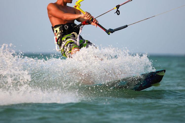 Man wakeboarding in sea against sky