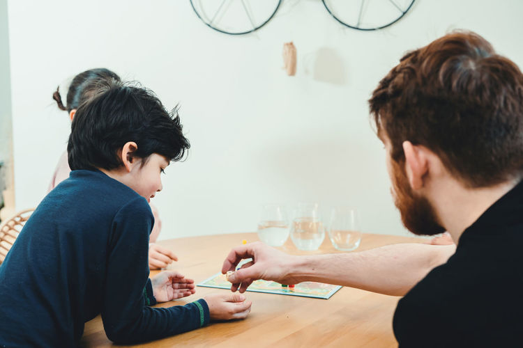 Rear view of father and son playing on table