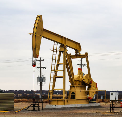 Large Yellow 912 Pump Jack on oil or gas well with surrounding equipment against an overcast sky Crude Natural Gas Oklahoma Production Crude Oil Drilling Drilling Rig Engery Engineering Fracking Fuel And Power Generation Geology Industry Large Group Of People Oil Oil Industry Oil Pump Oil Rig Oil Well Peak Oil Petroleum Pump Jack Pumping Oil Pumpjack Rig