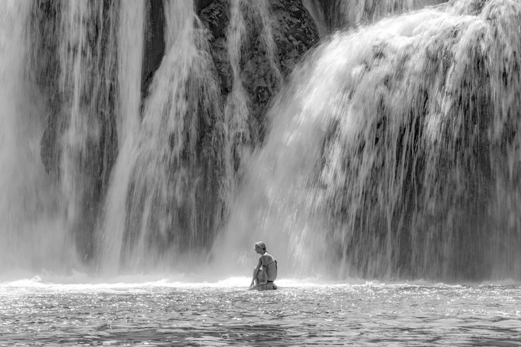 Woman sitting on rock against waterfall