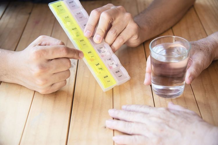 Close-up of hand holding glass of water by person with pill box on table