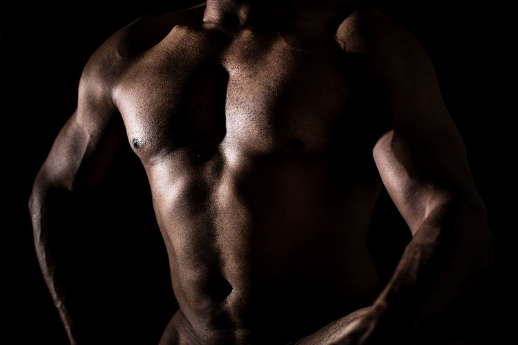 Midsection of shirtless bodybuilder man standing against black background