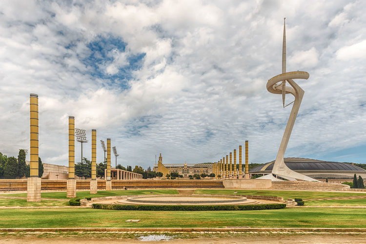 BARCELONA - AUGUST 11: The scenic and essential architecture of the Olympic Park on Montjuic hill, Barcelona, Catalonia, Spain, on August 11, 2017 Cloud - Sky Sky Built Structure Architecture Building Exterior Nature Day Travel Destinations No People Grass Outdoors Travel Plant The Past History Tall - High Tourism Landscape City Architectural Column