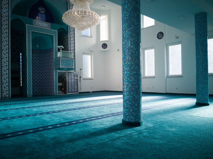 Illuminated lights on tiled floor by building