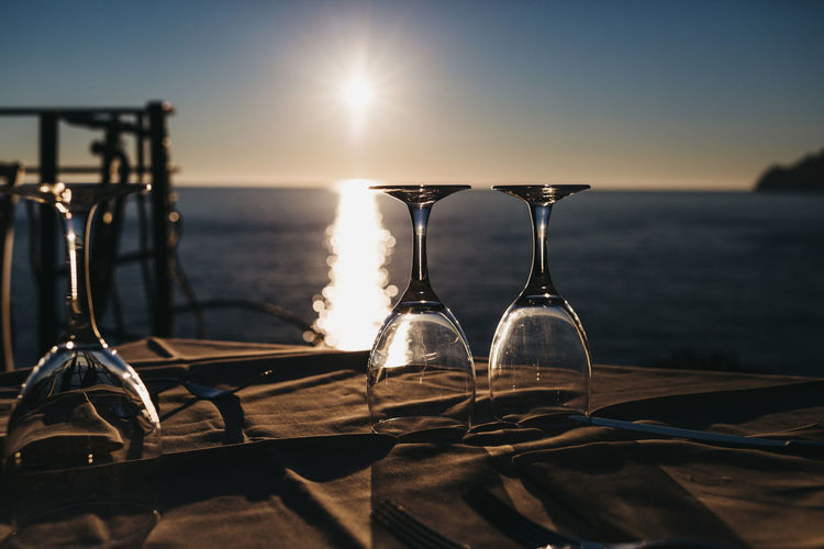 Wine glass on table by sea against sky during sunset