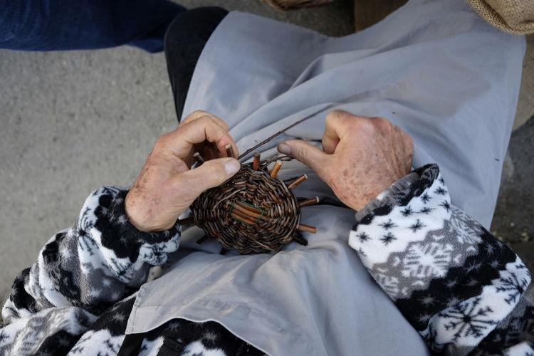 Midsection of male worker preparing wicker basket