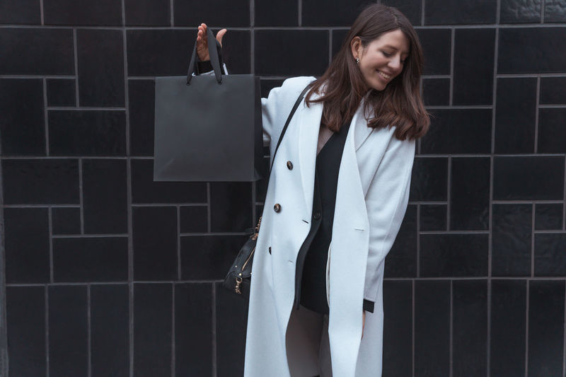 Smiling woman holding bag against wall outdoors