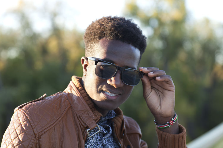 Handsome young black man with sunglasses and a leather jacket African American Autumn Leather Looking At Camera Sunlight Young Black Confident  Fall Focus On Foreground Handsome Jacket Kenyan Milennial One Person Outdoors Selective Focus Smiling Sunglasses Young Adult