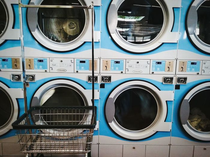 Close-up of laundry basket in front of washing machines at laundromat