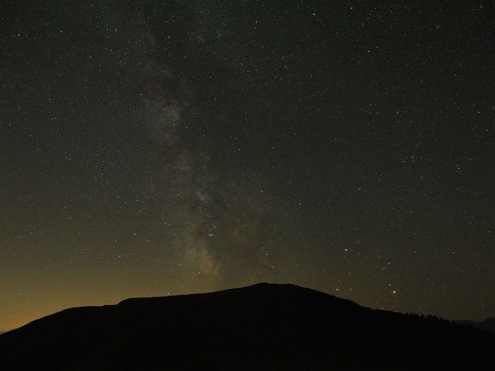 Scenic view of star field above silhouette mountains at night
