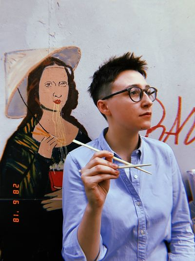 Young man wearing eyeglasses standing against wall