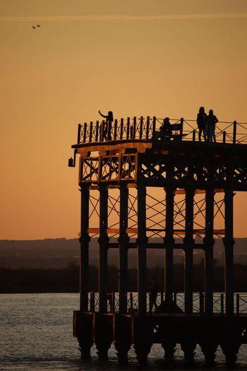 Silhouette people standing on pier by sea against orange sky
