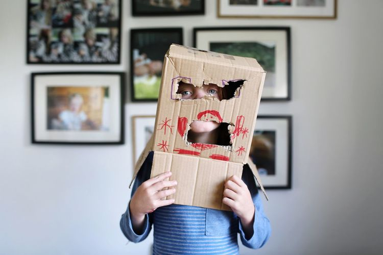 Portrait of playful girl with cardboard box on head at home