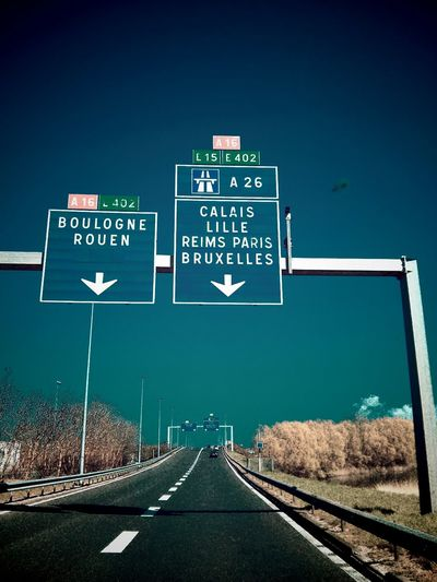 Road Sign On Highway Against Clear Sky