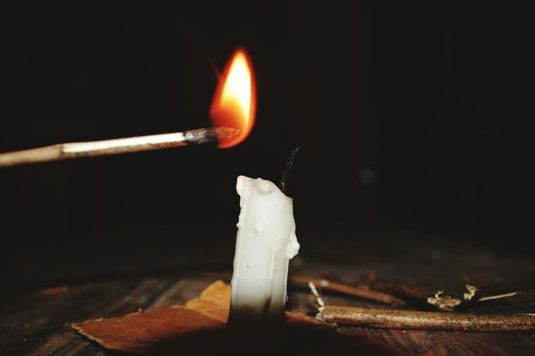 Close-Up Of Illuminated Matchstick With Candle On Table