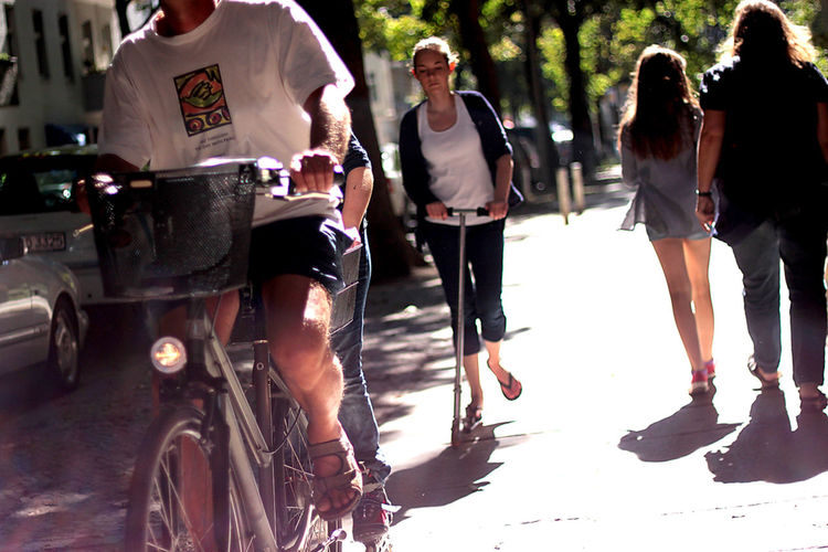 strret scene with bike and scooter in Berlin Bike Blur Casual Clothing Celebrate Your Ride Enjoyment Fun Lifestyles Light Motion Paople Real People Scooter Selective Focus Street Summer Transportation Young Adult