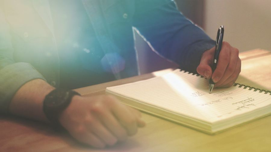 Midsection of man writing in diary