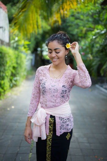 Beautiful Young Woman Wearing Flower On Ear While Standing On Footpath