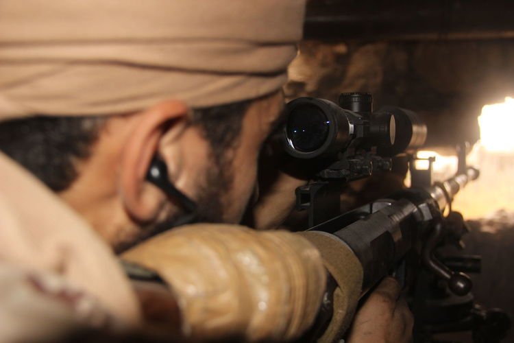Close-up of soldier aiming with gun