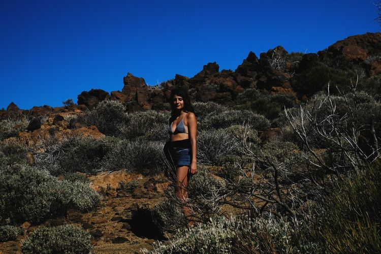 Beautiful woman standing on rock against sky