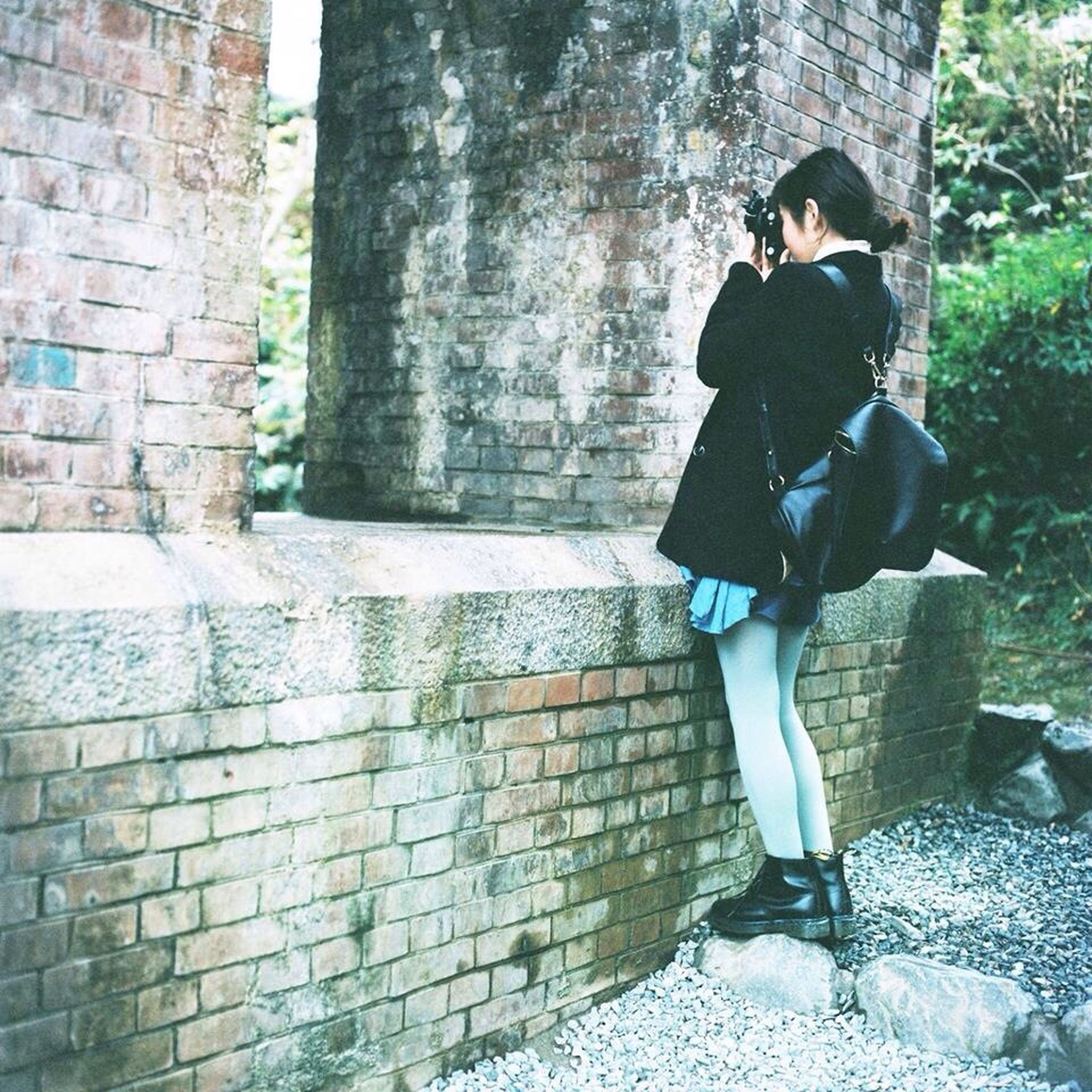 young adult, lifestyles, standing, casual clothing, full length, leisure activity, young women, wall - building feature, front view, person, architecture, built structure, brick wall, three quarter length, stone wall, building exterior, wall