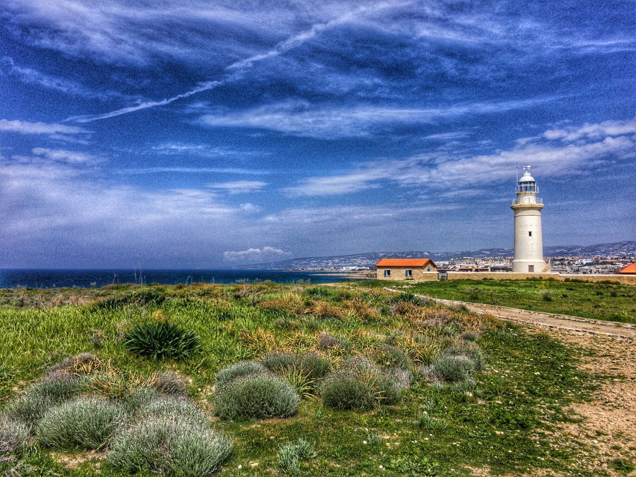 lighthouse, architecture, built structure, building exterior, sea, cloud - sky, grass, sky, guidance, day, protection, nature, horizon over water, scenics, beach, tranquility, no people, outdoors, beauty in nature, water
