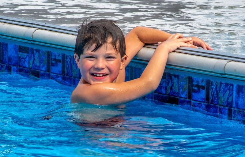 Portrait of happy boy swimming in pool