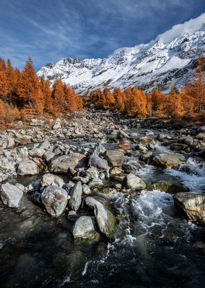 Scenic view of stream amidst rocks against sky during winter