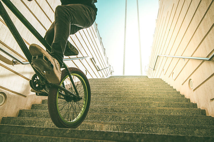 Low section of person with bicycle on staircase