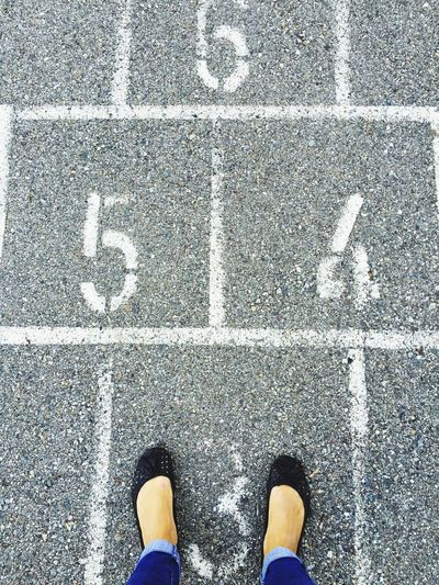 Low section of woman standing on hopscotch