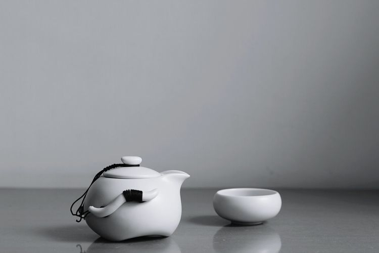Tea kettle and bowl on table against wall