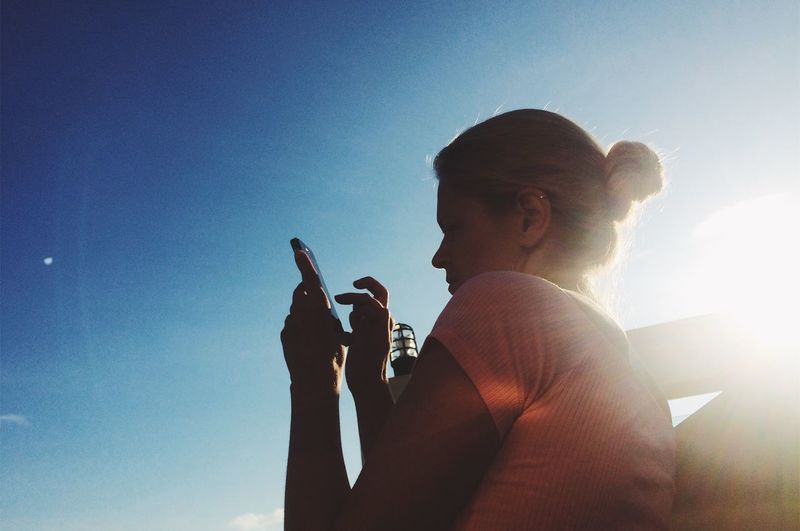 Woman Using Mobile Phone Against Blue Sky