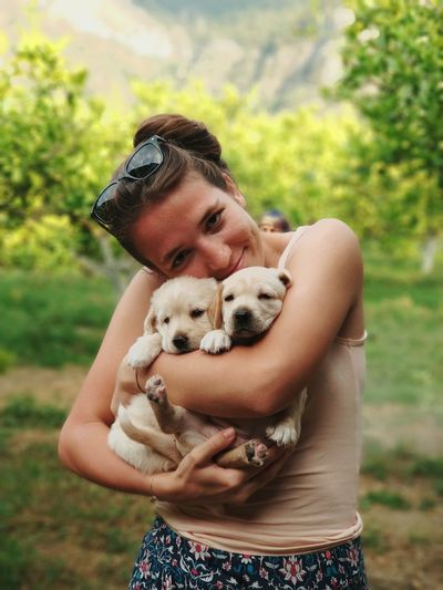 Portrait Of Woman Holding Puppies While Standing At Park