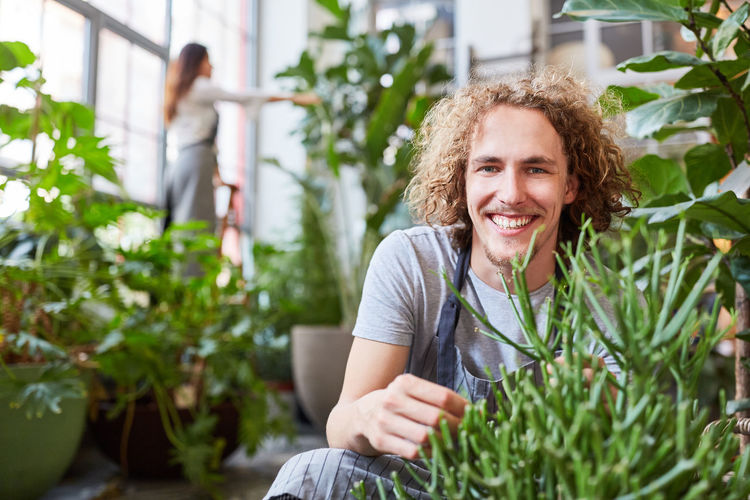 Portrait of smiling young woman holding plants