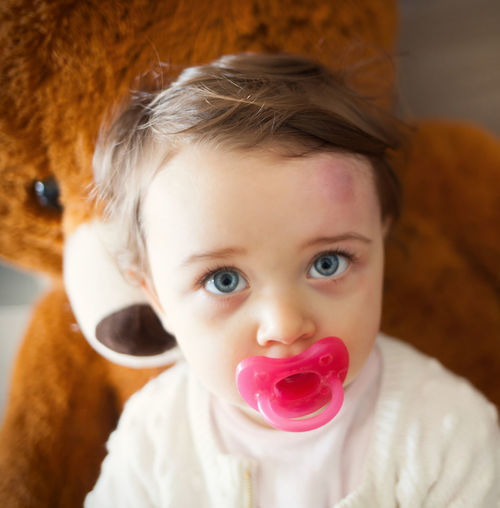 Close-up of cute girl with pacifier looking away at home