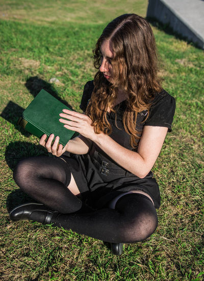 Young woman sitting in the grass reading a book. One Person Nature White Woman Young Adult Portrait Curly Hair Freckles Black Dress Caucasian Candid Real People Smart Intelligent Intelligence Lifestyle Reading Green Outdoors Tranquility Sunny Day Beautiful Book Sitting Grass Full Length Casual Clothing Long Hair Green Color Contemplation Lifestyles Leisure Activity Studying Learning